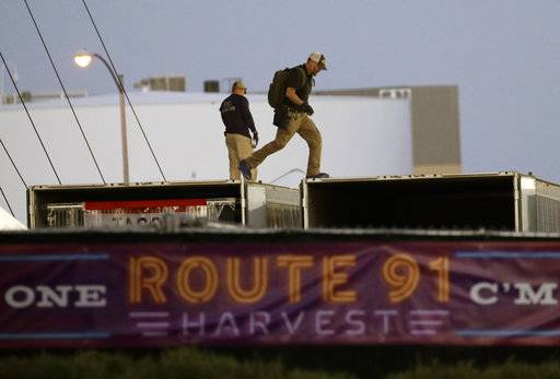 FBI agents walk on the roof of boxes inside the concert grounds where a mass shooting occurred in Las Vegas, Tuesday, Oct. 3, 2017. Authorities are trying to determine why Stephen Paddock, a 64-year-old high-stakes gambler and retired accountant, killed dozens of people at Route 91 Harvest, a country music festival, Sunday in Las Vegas.