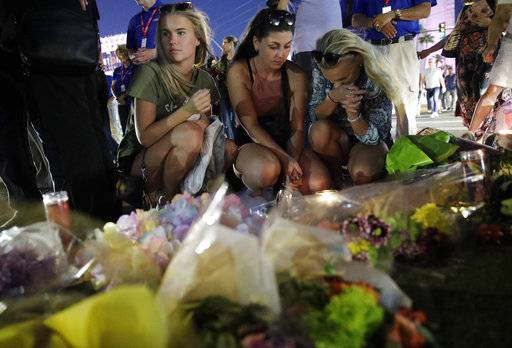 People pause at a memorial set up for victims of a mass shooting in Las Vegas, Nev., on Tuesday, Oct. 3, 2017. A gunman opened fire on an outdoor music concert on Sunday. It was the deadliest mass shooting in modern U.S. history, with dozens of people killed and hundreds injured, some by gunfire, some during the chaotic escape.