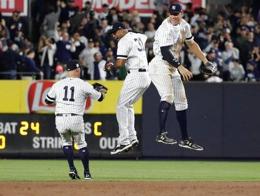 New York Yankees' Aaron Judge, right, celebrates with Aaron Hicks, center, as Brett Gardner, left, watches after the Yankees defeated the Minnesota Twins 8-4 in the American League wild-card baseball playoff game, early Wednesday, Oct. 4, 2017, in New York.