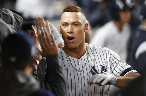 New York Yankees' Aaron Judge celebrates in the dugout with teammates after hitting a two-run home run during the fourth inning of the American League wild-card playoff baseball game against the Minnesota Twins in New York, Tuesday, Oct. 3, 2017.
