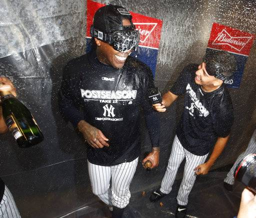 A teammate, right, interviews New York Yankees relief pitcher Aroldis Chapman during a locker room celebration after the Yankees defeated the Minnesota Twins 8-4 in the American League wild-card playoff baseball game in New York, early Wednesday, Oct. 4, 2017.