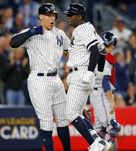 New York Yankees' Aaron Judge, left, and Didi Gregorius celebrate at the plate after Judge scored on Gregorius' first-inning, three-run home run in the American League wild-card playoff baseball game against the Minnesota Twins in New York, Tuesday, Oct. 3, 2017.