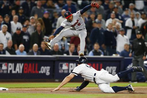 New York Yankees' Aaron Judge, right, slides safely into third as Minnesota Twins third baseman Eduardo Escobar leaps to avoid him during the seventh inning of the American League wild-card playoff baseball game in New York, Tuesday, Oct. 3, 2017.