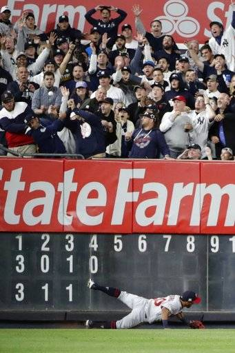 Minnesota Twins left fielder Eddie Rosario falls at the wall while chasing a two-run home run by New York Yankees' Aaron Judge during the fourth inning of the American League wild-card baseball game Tuesday, Oct. 3, 2017, in New York.