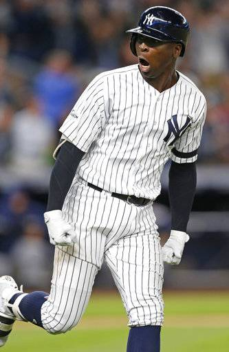 New York Yankees' Didi Gregorius reacts while running past the dugout on the way to first after hitting a three-run home run during the first inning of the American League wild-card playoff baseball game against the Minnesota Twins in New York, Tuesday, Oct. 3, 2017.