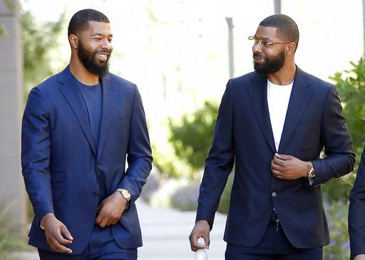 FILE in this Sept. 19, 2017 file photo, NBA players Markieff, left, and Marcus Morris arrive at Superior Court for the second day of their aggravated assault trial in Phoenix.  Jurors are expected to hear closing arguments Thursday, Sept. 28,  for the assault trial of the NBA players.  The Morris brothers are accused of helping three other people beat Erik Hood on Jan. 24, 2015.