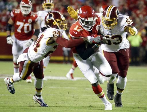Washington Redskins cornerback Josh Norman (24) and linebacker Zach Brown (53) tackle Kansas City Chiefs wide receiver Chris Conley (17) during the first half of an NFL football game in Kansas City, Mo., Monday, Oct. 2, 2017. Norman was injured on the play.
