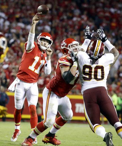 Kansas City Chiefs quarterback Alex Smith (11) throws as offensive lineman Eric Fisher (72) blocks Washington Redskins defensive lineman Ziggy Hood (90) during the second half of an NFL football game in Kansas City, Mo., Monday, Oct. 2, 2017.