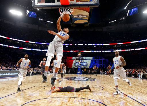 FILE- In this Feb. 20, 2017, file pool photo, Eastern Conference small forward Giannis Antetokounmpo, of the Milwaukee Bucks, dunks as Western Conference guard Stephen Curry, bottom, of the Golden State Warriors, lies on the court during the first half of the NBA All-Star basketball game in New Orleans. The NBA is scrapping the East against West format for its All-Star Game and will have captains pick teams this season.