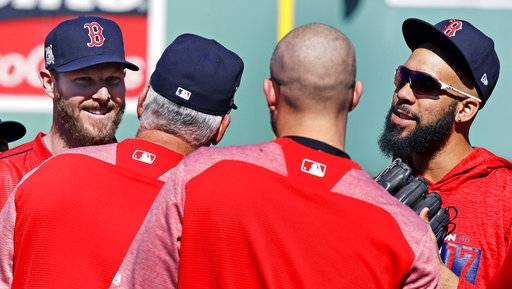 Boston Red Sox starting pitcher Chris Sale, left, and relief pitcher David Price, right, listen to pitching coach Carl Willis during a practice at Fenway Park in Boston, Tuesday, Oct. 3, 2017. The Red Sox face the Houston Astros in the American League Division playoff series.