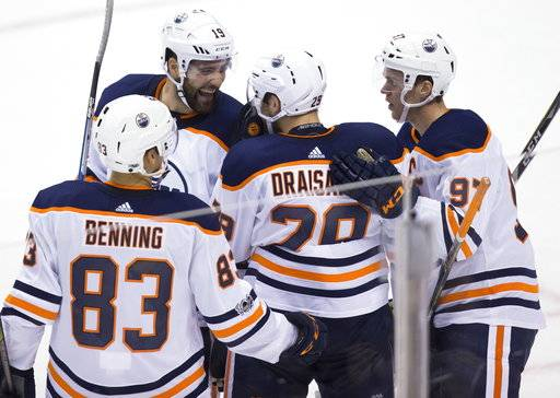 Edmonton Oilers' Matthew Benning, from left, Patrick Maroon, Leon Draisaitl, of Germany, and Connor McDavid celebrate Draisaitl's goal against the Vancouver Canucks during the first period of a preseason NHL hockey game in Vancouver, British Columbia, Saturday, Sept. 30, 2017. (Darryl Dyck/The Canadian Press via AP)