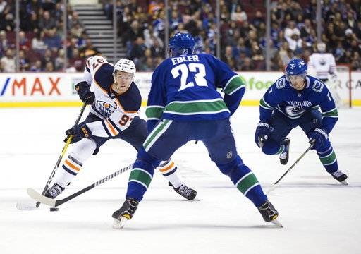 Edmonton Oilers' Connor McDavid, left, skates with the puck past Vancouver Canucks' Alexander Edler (23), of Sweden, as Jayson Megna, right, watches during the first period of a preseason NHL hockey game in Vancouver, British Columbia, Saturday, Sept. 30, 2017. (Darryl Dyck/The Canadian Press via AP)