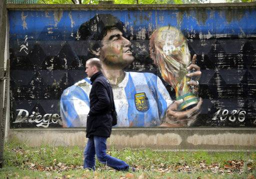 A man walks past a fence with graffiti depicting Argentina's soccer legend Diego Maradona in the town of Volkhov, 130 km (80 miles) east of St.Petersburg, Russia, Monday, Oct. 2, 2017.