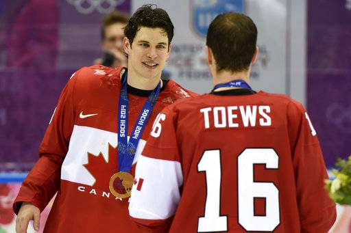 FILE - In this Feb. 23, 2014, file photo, Canada's Sidney Crosby, left, and Jonathan Toews wear their gold medals after beating Sweden 3-0 in the men's ice hockey final at the Sochi Winter Olympics in Sochi. Almost six months since the league announced it would skip the Pyeongchang Olympics, most of the NHL's best players are resigned to their missed opportunity. That Canada won't have Sidney Crosby and Jonathan Toews to go for the three-peat, that McDavid, Matthews and Eichel won't make their Olympic debuts quite yet. (Paul Chiasson, The Canadian Press via AP, File)