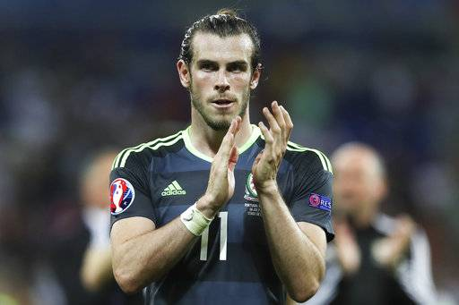 FILE - In this Wednesday, July 6, 2016 file photo, Wales's Gareth Bale acknowledges the fans at the end of their Euro 2016 semifinal soccer match against Portugal, at the Grand Stade in Decines-­Charpieu, France. They were the revelation of the 2016 European Championship, a Wales team of mostly journeymen - not counting its galactico, Gareth Bale - somehow reaching the semifinals of the country's first major soccer tournament in nearly 60 years. Their players virtually became overnight sensations. They were ahead of arch-rival England in the FIFA rankings, in 11th place when five years previously they were 117th. The comedown was sobering, if not entirely unexpected given the expectations foisted upon them.