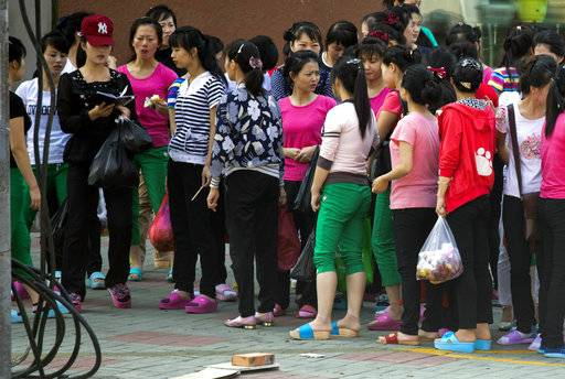 In this Sept. 2, 2017, photo, North Korean workers from the Hong Chao Zhi Yi garment factory gather for a head count after shopping at a street market in the city of Hunchun in northeastern China's Jilin province. The vast majority of the workers in Hunchun are women in their 20s. They arrive in China already divided into work teams, each led by a North Korean overseer, and remain isolated even from their own employers. Privacy is forbidden and they cannot leave their compounds without permission. When allowed to leave their compounds, they go to the city's working-class street markets.