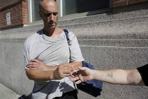 "In this Thursday, Aug. 17, 2017 photo Darren Killeen, 45, speaks with a reporter on the street near a strip of land sometimes referred to as ""Methadone Mile,"" in Boston. Residents and those recovering from drug addiction say the area has seen little to no improvement after city officials promised new measures to tackle the notorious drug haven last summer."
