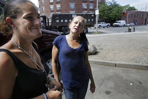 "In this Wednesday, Aug. 23, 2017 photo Jamie Allison, left, stands with a resident of the Mattapan neighborhood of Boston, on the street near a strip of land sometimes referred to as ""Methadone Mile,"" in Boston. Tobin says she is in a methadone program, and had just come from Narcotics Anonymous meeting when she ran into Allison."