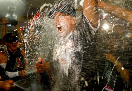 Arizona Diamondbacks manager Torey Lovullo is sprayed by his team after the National League wild-card playoff baseball game against the Colorado Rockies, Wednesday, Oct. 4, 2017, in Phoenix. The Diamondbacks won 11-8 to advance to an NLDS against the Los Angeles Dodgers.