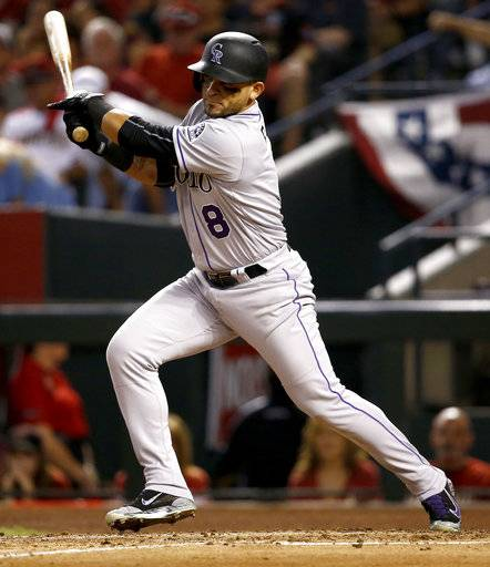 Colorado Rockies' Gerardo Parra follows through on an RBI base hit against the Arizona Diamondbacks during the fourth inning of the National League wild-card playoff baseball game, Wednesday, Oct. 4, 2017, in Phoenix.