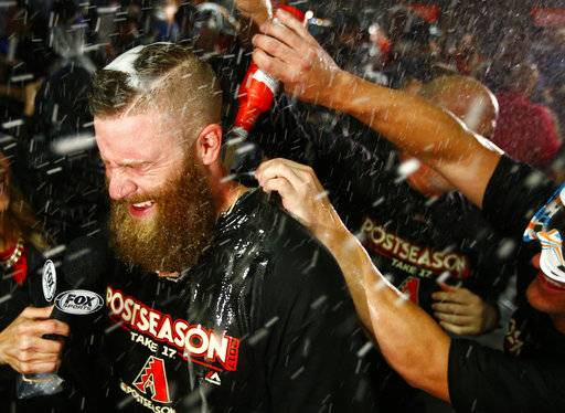 Arizona Diamondbacks relief pitcher Archie Bradley is doused by teammates after the National League wild-card playoff baseball game against the Colorado Rockies, Wednesday, Oct. 4, 2017, in Phoenix. The Diamondbacks won 11-8 to advance to an NLDS against the Los Angeles Dodgers.
