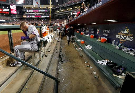 Colorado Rockies shortstop Trevor Story sits in the dugout as the Arizona Diamondbacks celebrate after the National League wild-card playoff baseball game Wednesday, Oct. 4, 2017, in  Phoenix. The Diamondbacks won 11-8 to advance to an NLDS against the Los Angeles Dodgers.