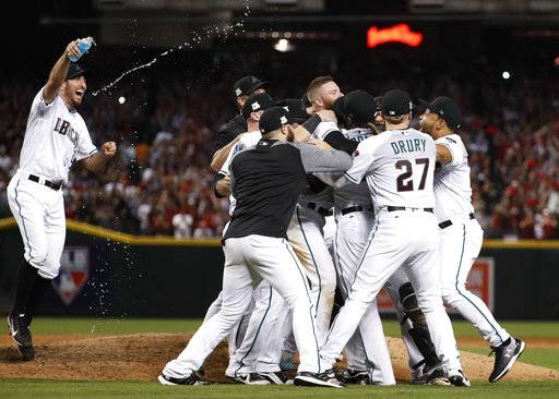 The Arizona Diamondbacks celebrate after the National League wild-card playoff baseball game against the Colorado Rockies, Wednesday, Oct. 4, 2017, in Phoenix. The Diamondbacks won 11-8 to advance to an NLDS against the Los Angeles Dodgers.