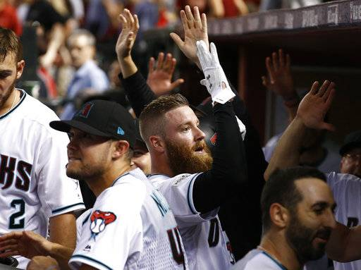 Arizona Diamondbacks' Archie Bradley, center, celebrate his two-run triple against the Colorado Rockies during the seventh inning of the National League wild-card playoff baseball game, Wednesday, Oct. 4, 2017, in Phoenix.