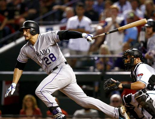 Colorado Rockies' Nolan Arenado follows through on a base hit against the Arizona Diamondbacks during the fourth inning of the National League wild-card playoff baseball game, Wednesday, Oct. 4, 2017, in Phoenix.