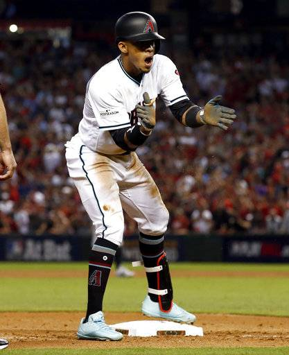 Arizona Diamondbacks' Ketel Marte applauds while looking to the dugout after hitting a triple against the Colorado Rockies during the fourth inning of the National League wild-card playoff baseball game, Wednesday, Oct. 4, 2017, in Phoenix.