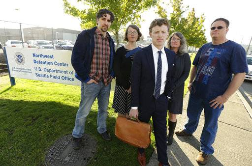 Tim Warden-Hertz, center, an attorney with the Northwest Immigration Rights Project who is representing Chong Kim, poses for a photo with friends and supporters of Kim, Wednesday, Oct. 4, 2017, outside the Tacoma Northwest Detention Center in Tacoma, Wash. An immigration judge Wednesday declined to release Kim from custody while Kim fights the government's efforts to deport him.