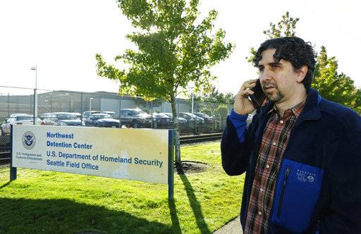 Matt Luce, a high-school friend of detained Iraq War veteran Chong Kim, talks to Kim on the phone, Wednesday, Oct. 4, 2017, outside the Tacoma Northwest Detention Center in Tacoma, Wash., where Kim is being held. An immigration judge Wednesday declined to release Kim from custody while he fights the government's efforts to deport him.