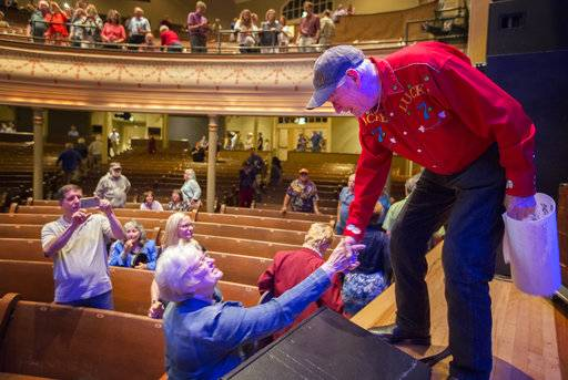 "In this May 7, 2016 photo, Russ Ringsak, longtime truck driver for Garrison Keillor's ""A Prairie Home Companion� public radio variety show,  greets fans after playing a song during the live broadcast as a farewell on his final show of the tour at the Ryman Auditorium in Nashville, Tenn.  Ringsak died Tuesday, Oct. 3, 2017 at his home in Stillwater, his wife, Denise Ringsak, told Keillor's Prairie Home Productions.  (Leila Navidi/Star Tribune via AP)"