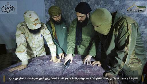 "FILE -- This undated file photo, shows Abu Mohammed al-Golani, second right, then leader of Fatah al-Sham Front, in pictures posted by the group, discussing battlefield details with field commanders over a map, in Aleppo, Syria. Russia's military announced Wednesday, Oct. 4, 2017, that it carried out airstrikes in Syria this week that critically wounded al-Golani, the leader of the al-Qaida-linked Levant Liberation Committee and killed 12 other militant commanders. Writing in Arabic  banner reads, ""Sheik Abu Mohammed al-Golani inspects military development and discusses them with military commanders as part of the battle for lifting the siege off Aleppo."" (Militant UGC via AP, file)"
