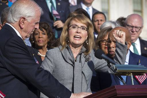Former Rep. Gabby Giffords of Arizona who survived an assassination attempt in 2011, flanked by Rep. Mike Thompson, D-Calif., left, and Rep. John Lewis, D-Ga., right, joins House Democrats in a call for action on gun safety legislation on the House steps Wednesday morning after the deadly mass shooting in Las Vegas this week, at the Capitol in Washington, Wednesday, Oct. 4, 2017.