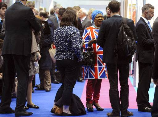 Delegates queue before attending a speech by the Conservative Party Leader and Prime Minister Theresa May, during the Conservative Party Conference at Manchester Central, in Manchester, England, Wednesday, Oct. 4, 2017.