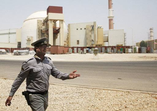 FILE - In this Aug. 21, 2010 file photo, an Iranian security officer directs media at the Bushehr nuclear power plant, with the reactor building seen in the background, just outside the southern city of Bushehr, Iran. A member of Iran's team of nuclear negotiators that struck the 2015 deal with world powers has been sentenced to five years in prison on espionage charges, a semi-official news agency reported on Wednesday, Oct. 4, 2017.