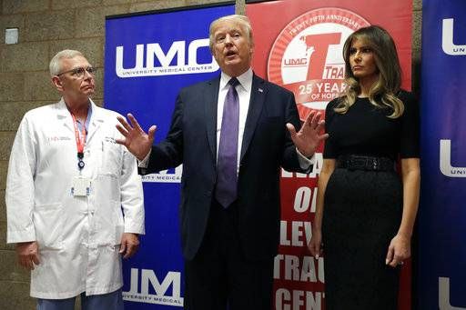 President Donald Trump talks as first lady Melania Trump and surgeon Dr. John Fildes listens at the University Medical Center after Trump met with survivors of the mass shooting Wednesday, Oct. 4, 2017, in Las Vegas.