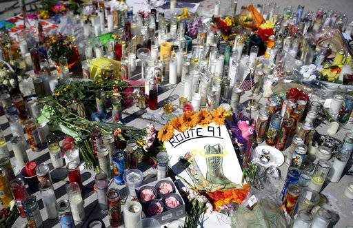 Flowers and candles are left at a makeshift memorial site on Las Vegas Boulevard on Tuesday, Oct. 3, 2017, in Las Vegas. A gunman opened fire on an outdoor music concert on Sunday killing dozens and injuring hundreds.