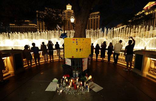 People take photos of the fountain at the Bellagio hotel in front of a memorial for victims of the mass shooting in Las Vegas, Tuesday, Oct. 3, 2017. A gunman opened fire on an outdoor music concert on Sunday. It was the deadliest mass shooting in modern U.S. history, with dozens killed and hundreds injured, some by gunfire, some during the chaotic escape.