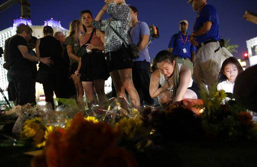 People pause at a memorial set up for victims of a mass shooting in Las Vegas, on Tuesday, Oct. 3, 2017. A gunman opened fire on an outdoor music concert on Sunday. It was the deadliest mass shooting in modern U.S. history, with dozens of people killed and hundreds injured, some by gunfire, some during the chaotic escape.