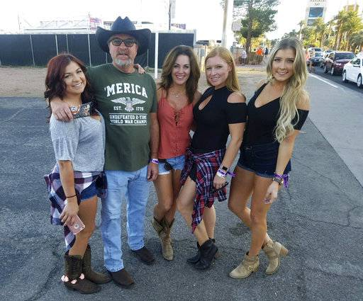 This Sunday, Oct. 1, 2017, photo provided by Tom Day Sr., shows his son Tom Day Jr, with Day Jr.'s family, at the Route 91 Harvest Festival in Las Vegas. Day Jr., was one of the people killed in Las Vegas after a gunman opened fire on Sunday, Oct. 1, 2017, at the music festival. (Courtesy of Tom Day Jr. via AP)