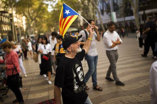 "A man waves an ""estelada"", or Catalonia independence flag, as he walks along the Ramblas in Barcelona, Wednesday, Oct. 4, 2017. Catalonia's regional government is mulling when to declare the region's independence from Spain in the wake of a disputed referendum that has triggered Spain's most serious national crisis in decades."