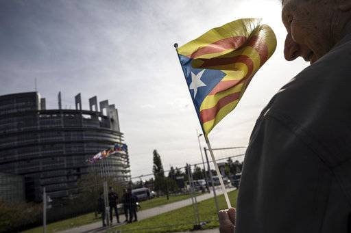 "A demonstrator waves a Catalan flag in support of the disputed independence vote Sunday in Catalonia during a gathering in front of the European Parliament in Strasbourg, eastern France, Wednesday, Oct. 4, 2017. European Commission Vice President Frans Timmermans says there is a ""general consensus that regional government of Catalonia has chosen to ignore the law when organizing the referendum."""