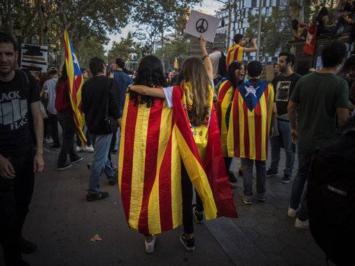 Two girls, one with a Catalan independence flag wrapped on her shoulders walks together with another one with a Spanish flag as demonstrators gather in downtown Barcelona, Spain, Tuesday Oct. 3, 2017. Thousands of people are demonstrated in Barcelona in protest at what they say was police brutality during a referendum on Catalonia's secession from Spain that was previously declared illegal by Spain's Constitutional Court.