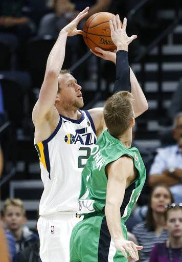 Utah Jazz forward Joe Ingles (2) shoots as Maccabi Haifa forward Willy Workman, right, during the first half of a preseason NBA basketball game Wednesday, Oct. 4, 2017, in Salt Lake City.