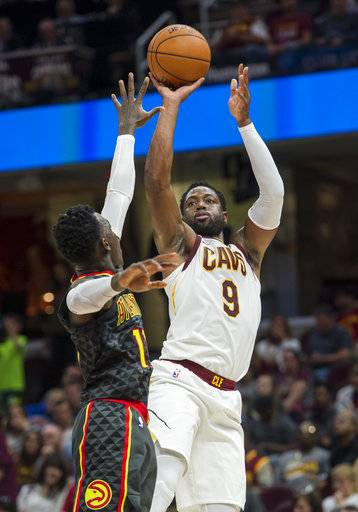 Cleveland Cavaliers' Dwayne Wade (9) shoots over Atlanta Hawks' Dennis Schroder during the first half of an NBA pre-season basketball game in Cleveland, Wednesday, Oct. 4, 2017.
