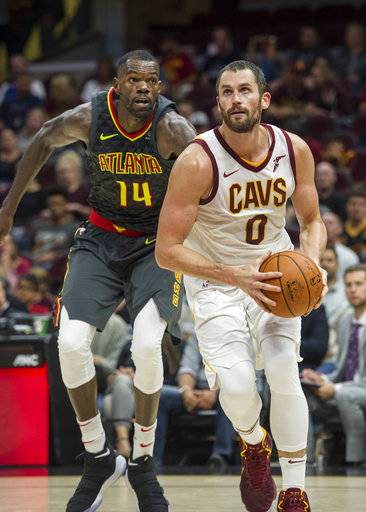 Cleveland Cavaliers' Kevin Love (0) drives past Atlanta Hawks' Dewayne Dedmon (14) during the first half of an NBA pre-season basketball game in Cleveland, Wednesday, Oct. 4, 2017.