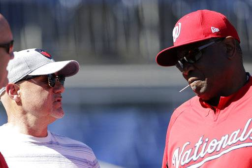 Washington Nationals' general manager Mike Rizzo, left, talks with manager Dusty Baker, right, during a baseball workout at Nationals Park, Wednesday, Oct. 4, 2017, in Washington. The Nationals host the Chicago Cubs in Game 1 of the National League Division Series on Friday.