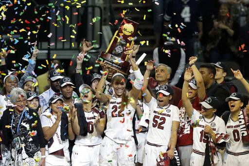 FILE - In this April 2, 2017, file photo, South Carolina forward A'ja Wilson (22) holds up the trophy as she celebrates with teammates after their win over Mississippi State in the final of the NCAA women's Final Four college basketball tournament, in Dallas. Reigning national champion South Carolina leaves behind last year's celebrations and starts preparations this week for a season the Gamecocks hope brings more trophies and cut-down nets their way.